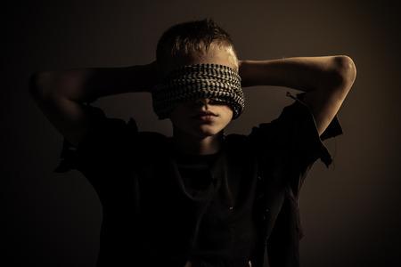 Vooraanzicht op blond mannelijk kind met dikke blinddoek rond hoofd en handen achter hem in slecht verlichte kamer Stockfoto
