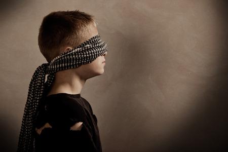 ojos vendados: Vista lateral de perfil de muchacho serio con los ojos vendados, con copia espacio delante de �l para el concepto sobre el secuestro o toma de rehenes
