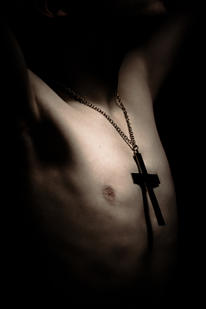 Lighted bare chest of boy wearing large chain and crucifix symbol with arms up in dimly lit area