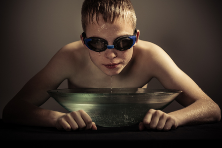 submerging: Serious shirtless soaking wet blond boy in goggles with face over wide brim bowl of water