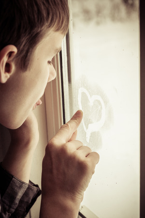 lovelorn: Close up on teenage boy writing with finger to make heart symbol shape in mist on window
