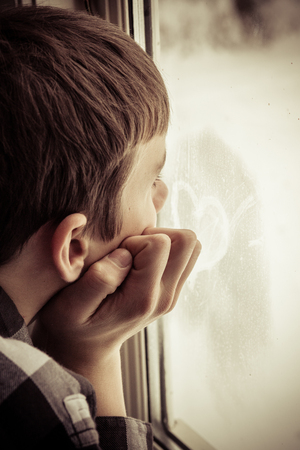 Partial side view of unidentifiable teenage boy looking out window with hand on side of face toward heart symbol shape written on glass Stock Photo
