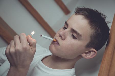 Experimentelle gekippt Bild des Jungen mit kurzen Haaren und einem weißen Hemd im Treppenhaus mit Zigarette und zündete leichter