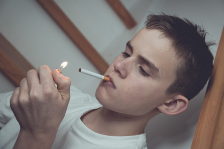 Experimental tilted image of boy with short hair and white shirt in stairwell with cigarette and lit lighter