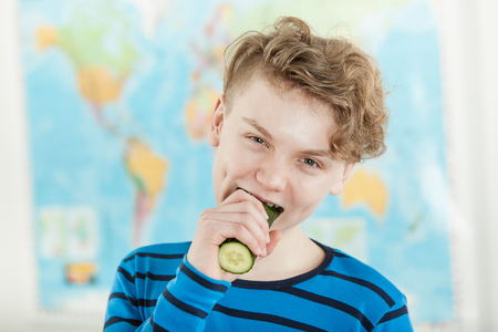 Head and Shoulders Portrait of Young Teenage Boy Wearing Blue and Black Striped Shirt Taking Bite of Whole Cucumber and Standing in Room with Map of World Hanging on Wall in Background Stock Photo