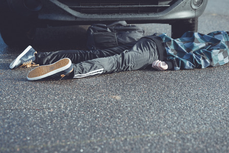 Close Up of Unrecognizable Car Accident Fatality - Bottom Half and Legs of Young Teenage Boy Car Accident Victim Lying on Wet Road Pavement in front of Stopped Vehicle Stock Photo