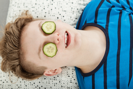 revitalizing: High Angle View of Young Teenage Boy Lying Down on Back and Relaxing with Cucumber Slices on Eyes to Reduce Swelling and Puffiness