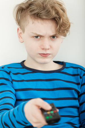 Sulky petulant young boy watching television holding out the remote control to change programs with a cross frown Stock Photo