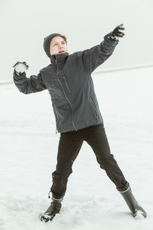 throw up: Full Length View of Young Teenage Boy Wearing Warm Clothing and Rubber Boots Winding Up to Throw Snowball Outside on Chilly Overcast Winter Day