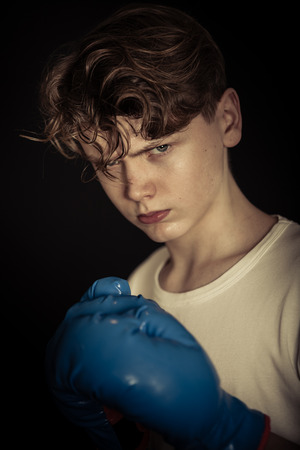 boxing boy: Close Up Portrait of Angry Young Teenage Boy Wearing White T-Shirt and Blue Boxing Gloves Glaring at Camera in Dark Studio - Ready to Fight