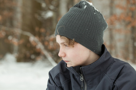 introspective: Side Profile Close Up Portrait of Serious Young Teenage Boy Wearing Jacket and Gray Knitted Hat Staring to the Side on Overcast Winter Day with Copy Space