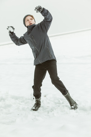 Full Length View of Young Teenage Boy Wearing Warm Clothing and Rubber Boots Winding Up to Throw Snowball Outside on Chilly Overcast Winter Day