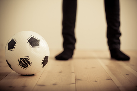 disobedient: Close Up of Unidentifiable Person Legs Standing Out of Focus in Background in Black Socks and Pants with Soccer Football in Foreground with Copy Space Stock Photo