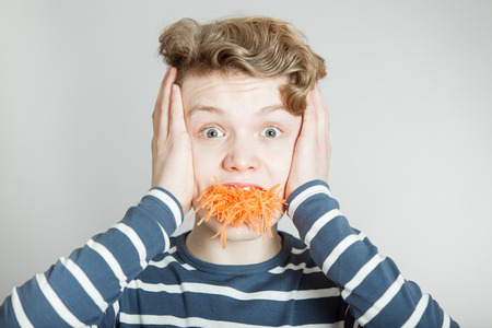 wide eyed: Goofy young boy with an overflowing mouthful of grated carrot holding his hands to his ears in wide eyed shock and amazement Stock Photo