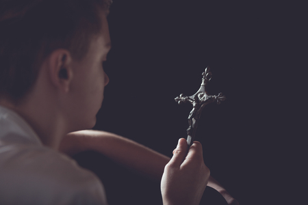 beliefs: Looking Over Shoulder of Young Teenage Boy Holding Ornate Religious Christian Cross in Hand and Contemplating Faith and Beliefs in Dark Studio with Copy Space