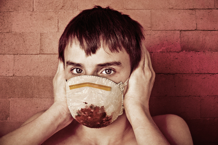 haemorrhage: Close Up of Young Sick Pre Teenage Boy with Bare Shoulders and Brown Hair Wearing Blood Soaked Surgical Mask and Covering Ears with Hands in front of Brick Wall - Contagious Disease Concept