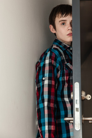 traumatized: Waist Up Portrait of Young Teenage Boy with Dark Brown Hair Wearing Colorful Plaid Shirt Standing Quietly Behind Door Inside Home and Staring Blankly at Camera