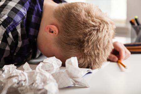 紙を台無しのしわくちゃのページに囲まれたテーブルで彼の頭に座って宿題に苦しんでいる少年 写真素材