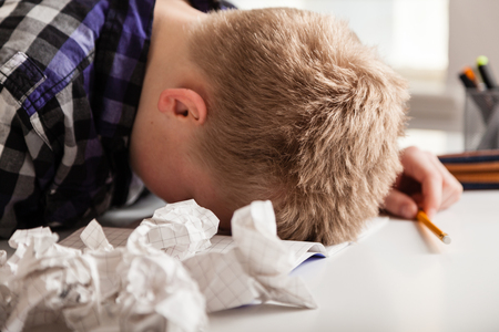Young boy struggling with his homework sitting with his head down on the table surrounded by crumpled pages of screwed up paper Stock Photo
