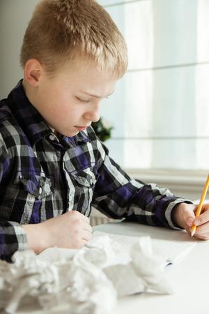 writer's block: Young boy with writers block struggling with his homework sitting staring at a blank sheet of paper with a pencil in his hand and numerous crumpled pages in the foreground