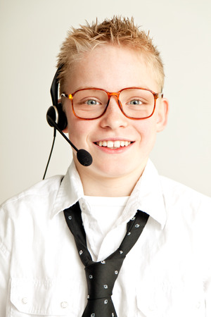 spiked hair: Occupation Concept Image - Head and Shoulders Portrait of Young Blond Pre Teenage Boy with Spiked Hair Smiling at Camera and Dressed as Businessman with Eye Glasses and Wearing Head Set Stock Photo