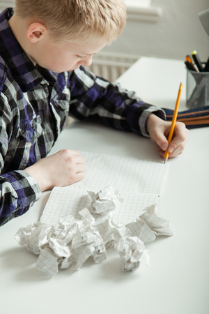 writer's block: Young teenage boy battling to complete his homework sitting staring at a blank notebook surrounded by discarded crumpled pages of paper, close up high angle view