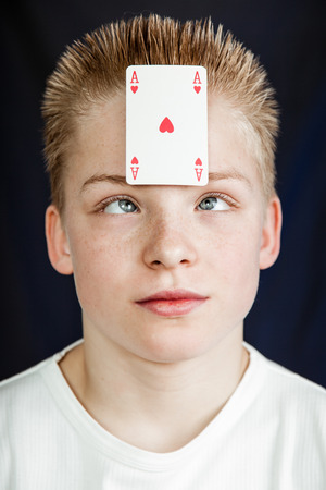 Head and Shoulders Close Up of Pre Teenage Boy with Spiked Blond Hair Looking Cross Eyed at Ace of Hearts Playing Card Stuck to Forehead in Studio with Dark Background