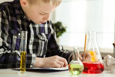 diligente: muchacho joven que hace su preparaci�n diligente ciencias escribir notas mientras se sienta en el pa�s con una gran variedad de art�culos de vidrio de laboratorio lleno de coloridos soluciones
