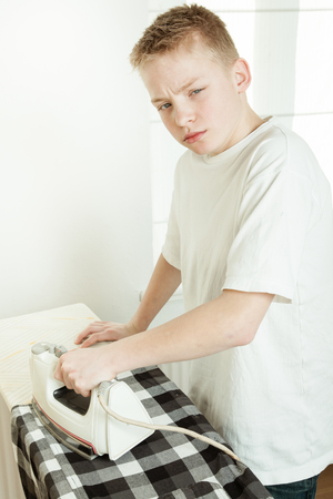 Waist Up View of Young Blond Pre Teenage Boy Looking Grumpy and Unhappy While Ironing Black and White Plaid Shirt - Doing Chores and Getting Ready Before Going Out to School