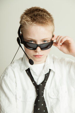 spiked hair: Occupation Concept Image - Head and Shoulders Portrait of Young Blond Pre Teenage Boy with Spiked Hair Dressed as Businessman and Wearing Head Set, Tilting Sunglasses Down