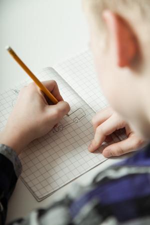 子供が左利き肩表示ページおよび彼の手の上でノートに書く宿題若い 10 代の少年 写真素材