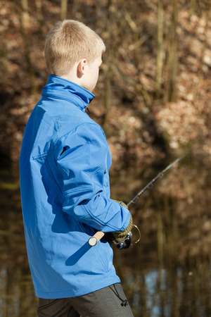 view from behind: View from behind of boy in blue jacket and gloves with fishing rod facing a pond during autumn Stock Photo