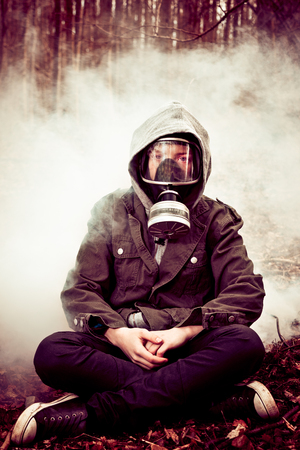 pollutants: Calm single boy in hooded jacket and jeans sitting on ground with crossed legs while surrounded by mysterious fog