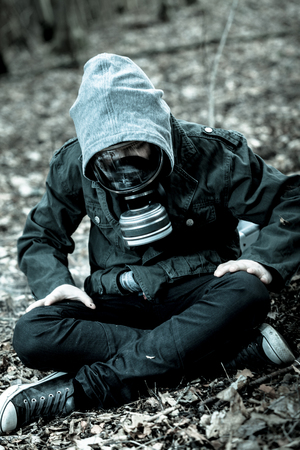 tense: Tense single boy in gas mask, jeans and hooded jacket sitting on ground with crossed legs while surrounded by fallen leaves