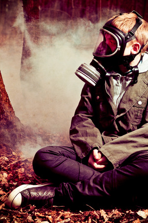 evocative: Calm single boy in gas mask, jeans and jacket sitting on ground with crossed legs while surrounded by mysterious fog