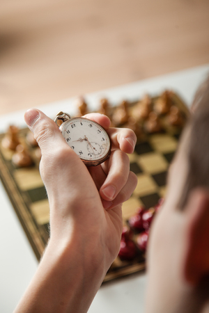 unidentifiable: Close Up Rear View of Unidentifiable Person Holding Stop Watch in Hand Above Chess Board Set for Game Out of Focus in Background - Timing Moves in Chess Game