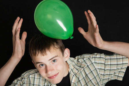 dark brown hair: High Angle Close Up of Young Teenage Boy with Dark Brown Hair Wearing Plaid Shirt Playing with Bright Green Balloon on Head in Studio with Dark Background, Smiling Up at Camera
