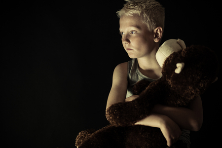 solemn: Close up on young introvert blond boy with depressed or solemn expression in dim light holding toy