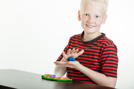 Happy young boy playing with a ball of bright colorful blue plastic putty rolling it in his hand to make it more malleable so that he can mold it for his design on the table