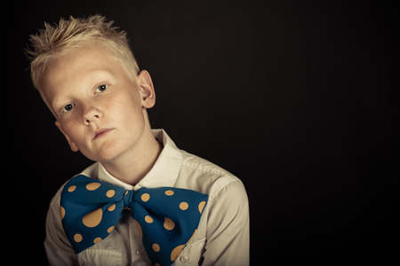 Serious little blond boy with spiky hair wearing funny blue bowtie with yellow dots over black background with copy space