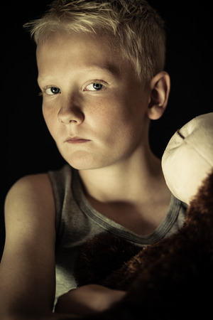 solemn: Close up on young single blond boy with depressed or solemn expression in dim light holding toy Stock Photo
