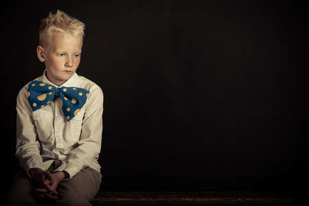 introspective: Sad little blond boy wearing spiky hair and funny blue bowtie with yellow dots over black background with copy space Stock Photo
