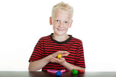 Happy young boy playing with colorful bright plastic modeling clay or putty creating an original design on the table in front of him