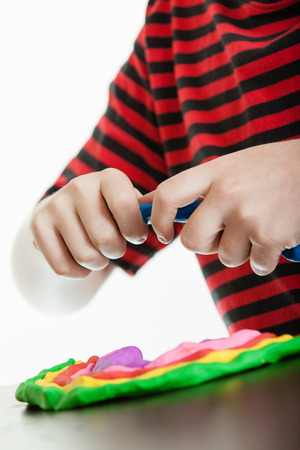 Colorful design of brightly colored pieces of modeling putty formed in to semi circle made by a young boy, close up view of the plastic putty design and his hands