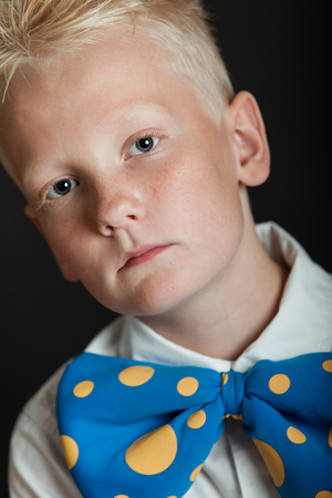 Serious little blond boy with spiky hair wearing funny blue bowtie with yellow dots over black background