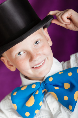 Handsome dapper little boy in a top hat and enormous blue and yellow polka dot bow-tie doffing his hand to the brim with a lovely sweet smile, close up cropped view