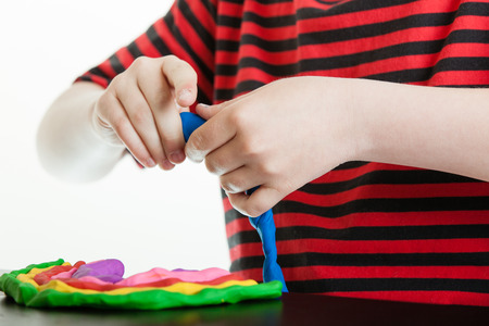 Hands of a young boy playing with bright colorful pieces of plastic putty molding it with his hands into tubes to incorporate into his design