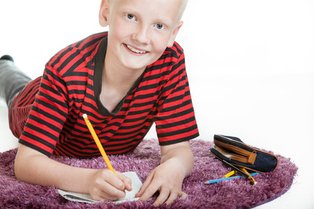 Smiling young boy doing his homework lying on a furry purple rug on the floor looking up and grinning at the camera, isolated on white with copy space