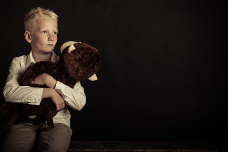 Single sad little blond male child with spiked hair holding large plush toy over black background