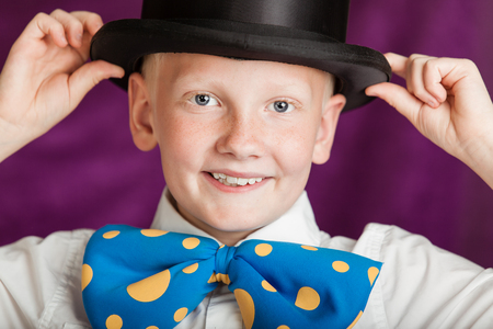 grins: Jaunty young boy in a large out sized blue polka dot bow-tie and top hat holding his hands to the brim as he grins playfully at the camera